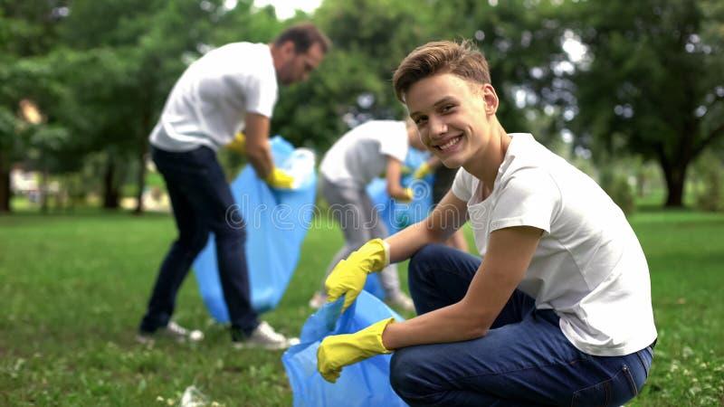 Волонтеры собирают сор, заботу подростка усмехаясь, экологическую и экологическую стоковая фотография