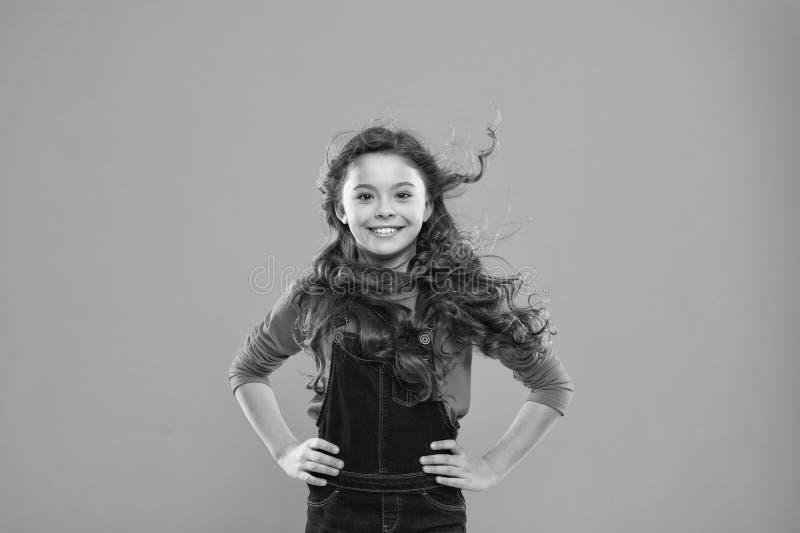 волосы девушки немногая длиной Сторона ребенк счастливая милая с прелестной стойкой вьющиеся волосы над голубой предпосылкой Чист стоковые изображения