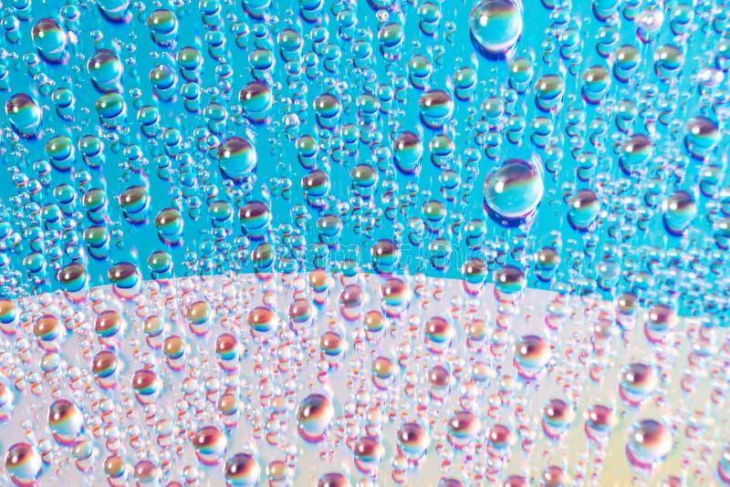 Вода падает на средства массовой информации dvd, падения воды на красочной предпосылке стоковые фотографии rf