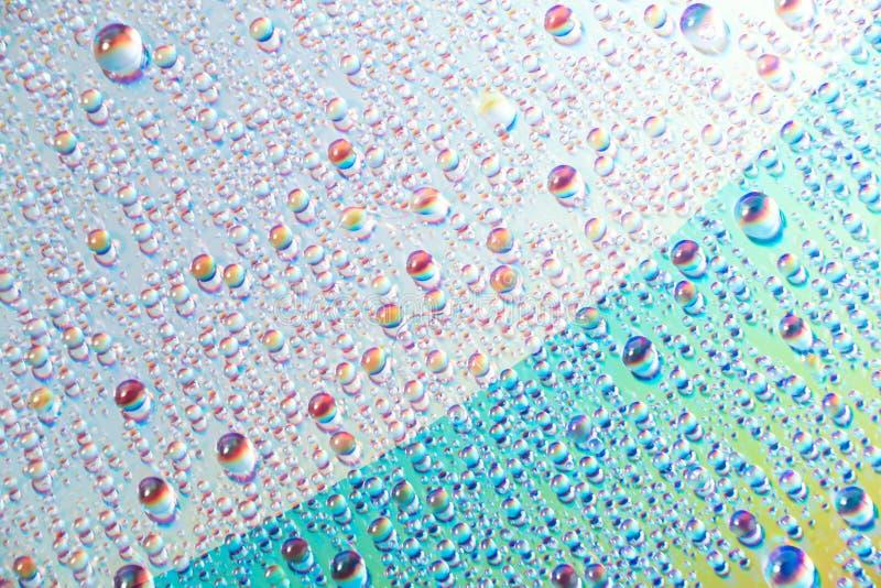 Вода падает на средства массовой информации dvd, падения воды на красочной предпосылке стоковое фото
