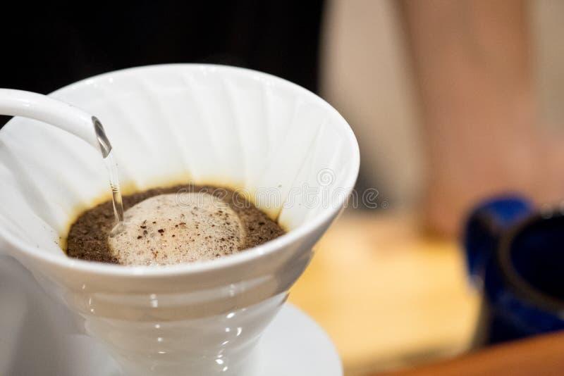 Вода человека лить от чайника в фильтр кофе стоковые фотографии rf