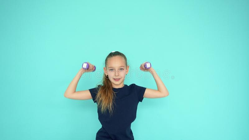 Гантель молодой девушки подростка поднимаясь на тренировке спортзала на предпосылке copyspace стоковое изображение rf