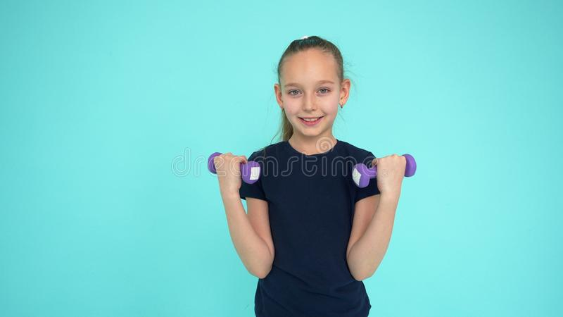 Гантель девушки фитнеса поднимаясь для тренируя мышц руки на зеленой предпосылке стоковое изображение