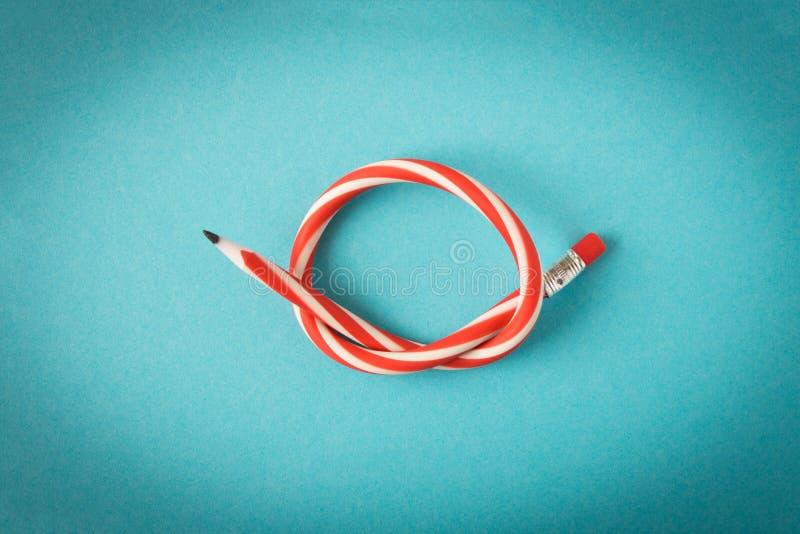 гибкий карандаш На голубой предпосылке Гнуть карандаш стоковое фото