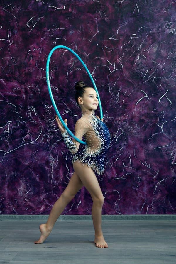 Гимнаст маленькой девочки в голубом костюме со стразами стоит на офисе фиолетовой стены, держа обруч за ее задней частью стоковые фотографии rf