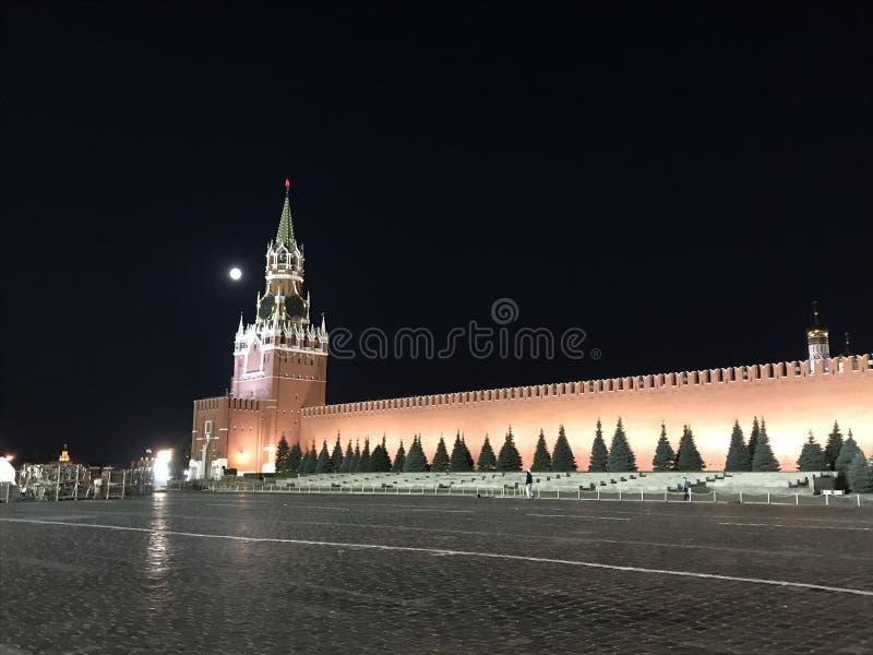 Главная башня Москвы Кремля, России с огромными час-перезвонами и стеной красного кирпича против черных ночного неба и полнолуния стоковые фото