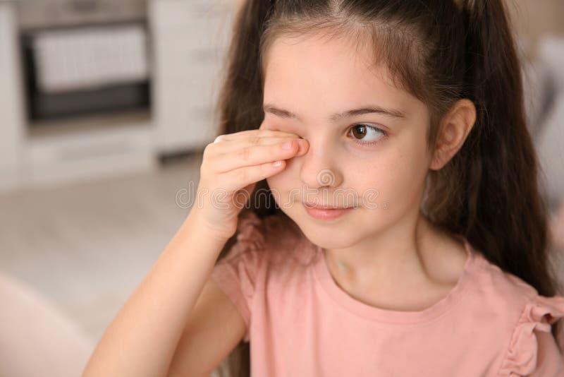 Глаз затирания маленькой девочки дома стоковые фото