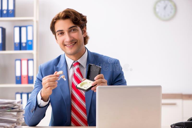 Глухой работник используя слуховой аппарат в офисе стоковые изображения