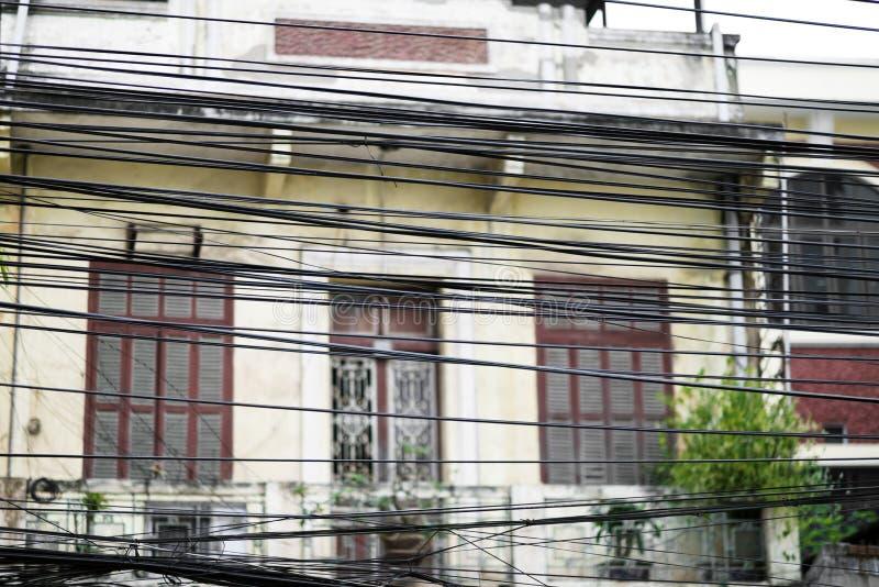 Грязная электрическая проводка, запутанная масса, который подвергли действию кабелей на улице в Ханое, Вьетнаме стоковые изображения rf