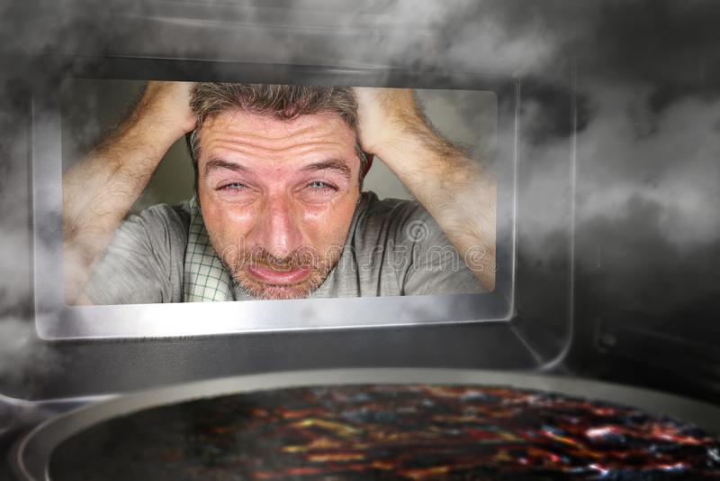 Грязный и смешной фиктивный переваренный человек в кухне смотря через горение микроволны или пиццы печи делающ беспорядок домашне стоковое фото rf