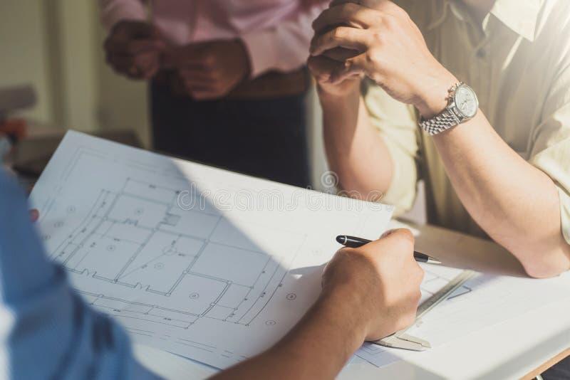 Группа в составе архитекторы обсуждая со светокопиями планирует в дизайне офиса Концепция конструкции и структуры стоковое фото rf