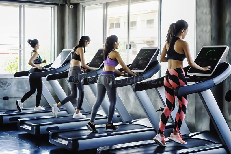 Группа в составе люди молодых женщин бежать на третбанах в современном спортзале спорта стоковая фотография