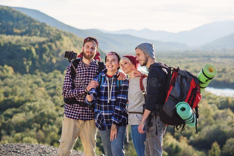 Группа в составе молодые усмехаясь люди путешествуя совместно в горах Счастливые путешественники хипстера с рюкзаками делая selfi стоковое изображение rf
