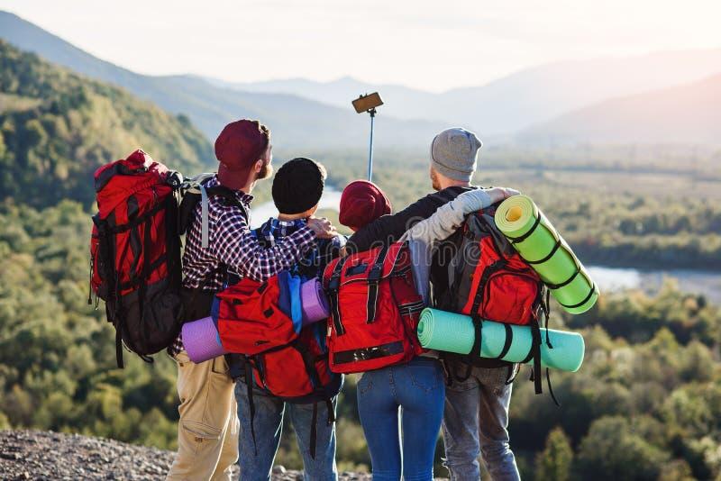 Группа в составе молодые усмехаясь люди путешествуя совместно в горах Счастливые путешественники хипстера с рюкзаками делая selfi стоковые изображения