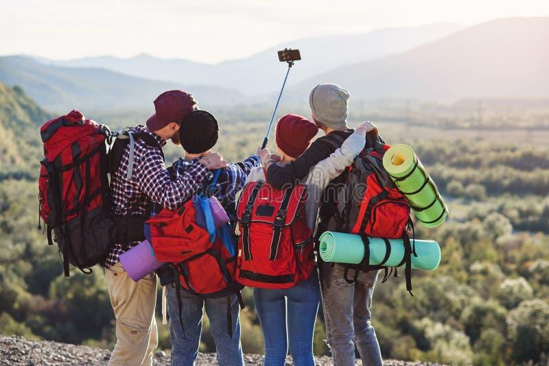 Группа в составе молодые усмехаясь люди путешествуя совместно в горах Счастливые путешественники хипстера с рюкзаками делая selfi стоковое изображение