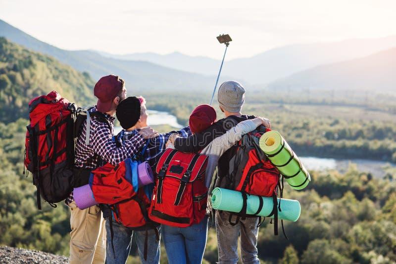 Группа в составе молодые усмехаясь люди путешествуя совместно в горах Счастливые путешественники хипстера с рюкзаками делая selfi стоковая фотография rf