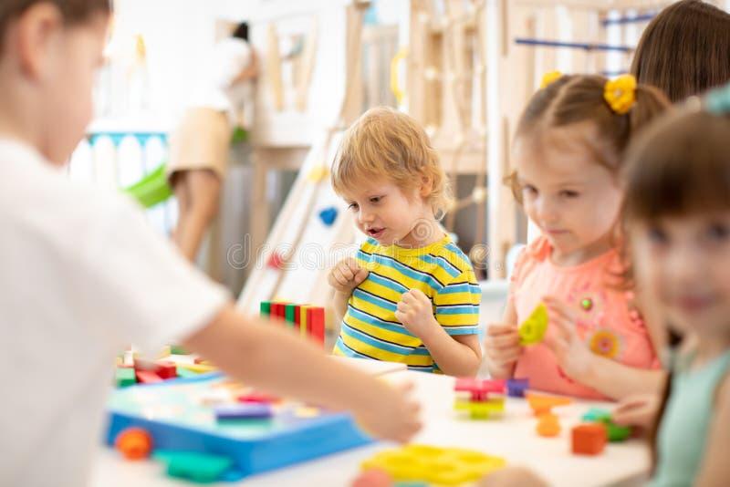 Группа в составе дети играя совместно в классе в детском саде или preschool стоковые изображения