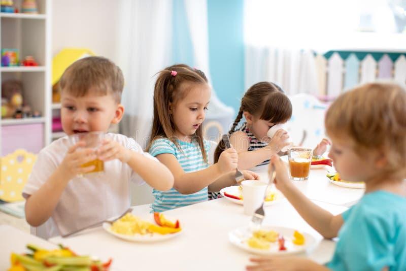 Группа в составе дети детского сада имеет обед стоковые фотографии rf