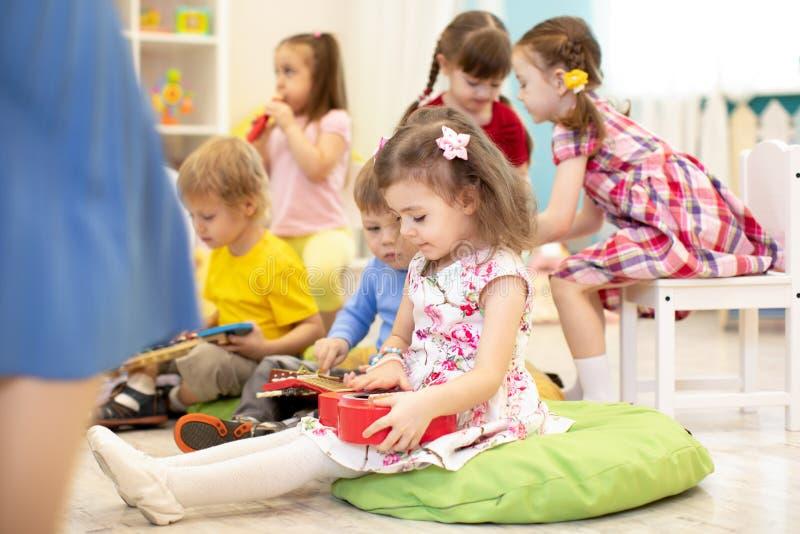 Группа в составе дети preschooler играет с музыкальными игрушками на детском саде стоковое фото