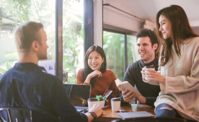 Группа в составе друзья беседуя и используя ноутбук в кафе на кафе кофейни в университете говоря и смеясь совместно стоковое изображение