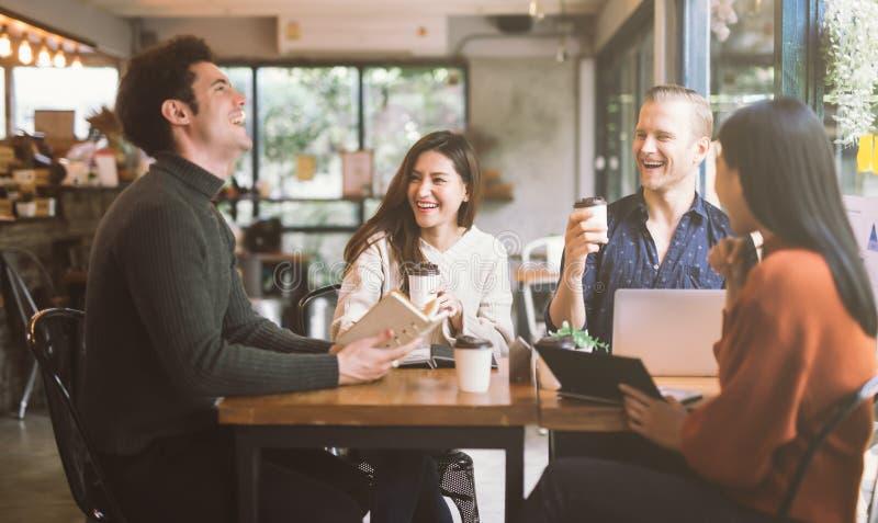 Группа в составе друзья беседуя и используя ноутбук в кафе на кафе кофейни в университете говоря и смеясь совместно стоковые изображения rf