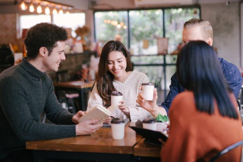 Группа в составе друзья беседуя и используя ноутбук в кафе на кафе кофейни в университете говоря и смеясь совместно стоковая фотография