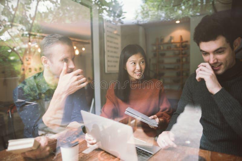 Группа в составе друзья беседуя и используя ноутбук стоковые изображения