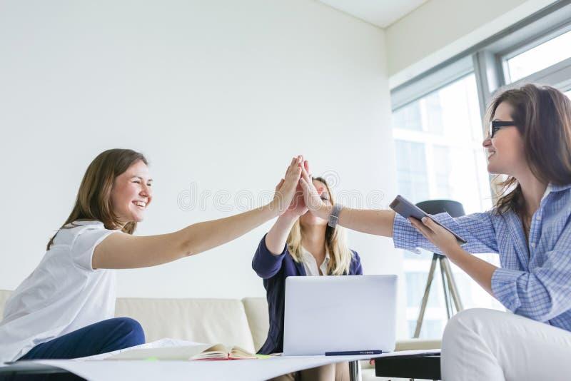 Группа в составе счастливые бизнес-леди празднует успех проекта стоковое изображение