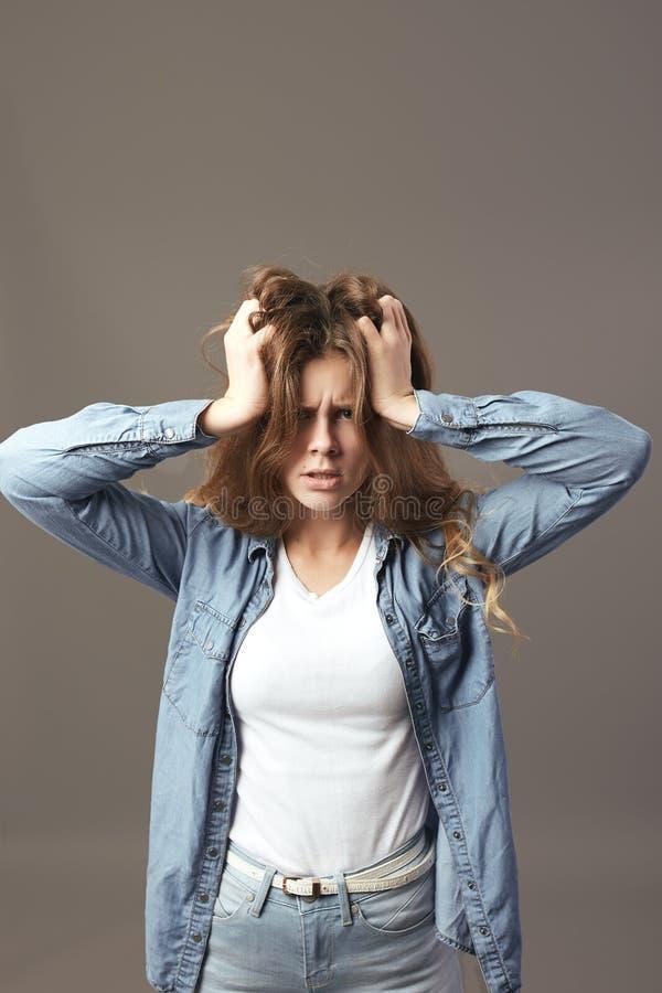 Грустная коричнев-с волосами девушка одетая в белых футболке и демикотоне держит ее руки на ее голове на серой предпосылке стоковое изображение rf