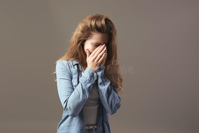 Грустная коричнев-с волосами девушка одетая в белых футболке и демикотоне держит ее руки на ее стороне на серой предпосылке стоковое фото rf