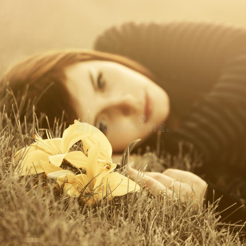 Грустная молодая женщина лежа на траве стоковые фотографии rf