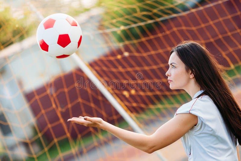 Голкипер женщины бросает положение шарика на цель футбола стоковое фото