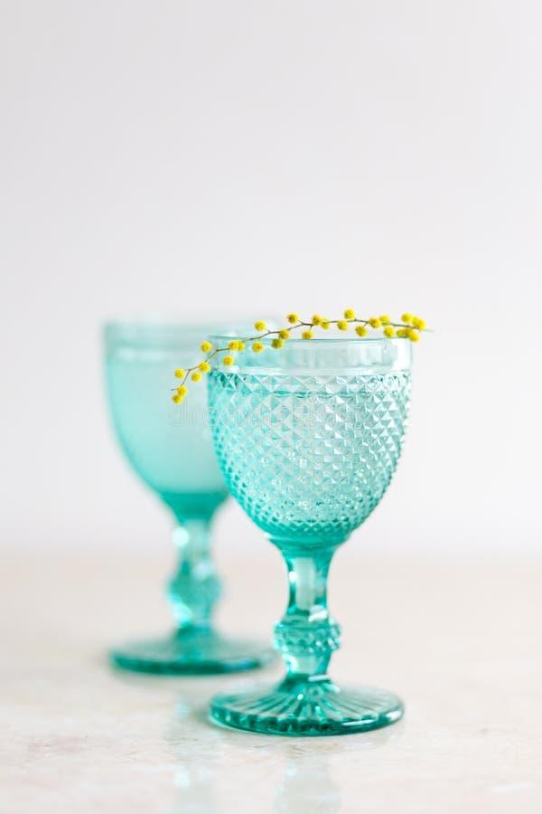 Голубые винтажные кубки и желтые цветки мимозы Рюмки на предпосылке whight стоковое фото