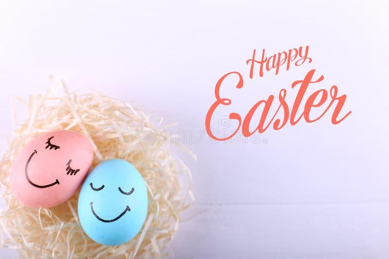 Голубые и розовые яйца с покрашенными улыбками в гнезде, космосе экземпляра Счастливый дизайн поздравительной открытки концепции  стоковое изображение rf
