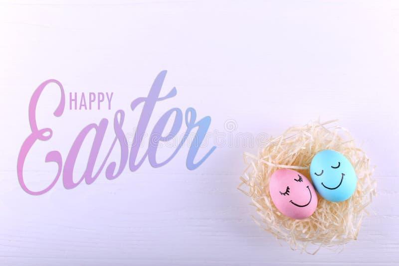 Голубые и розовые яйца с покрашенными улыбками в гнезде, космосе экземпляра Счастливый дизайн поздравительной открытки концепции  стоковое изображение