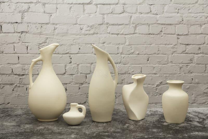 Гончарня, ваза, кувшин белой глины на серой каменной предпосылке Модель-макет гончарни сделанный из белой глины на серой предпосы стоковая фотография