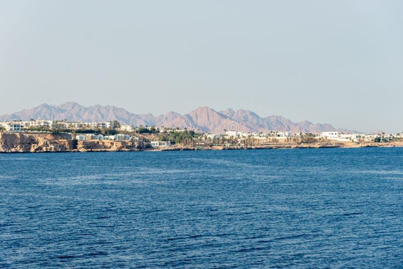 Гостиницы и дома в стойке расстояния над скалой над голубым морем стоковое изображение
