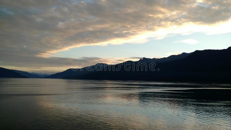 Горизонт заполненный горой на Тихом океане Внутренний проход Аляска на заходе солнца стоковые изображения