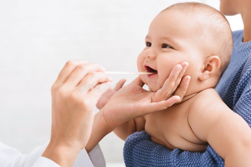 Горло педиатра доктора рассматривая newborn младенца стоковые фотографии rf