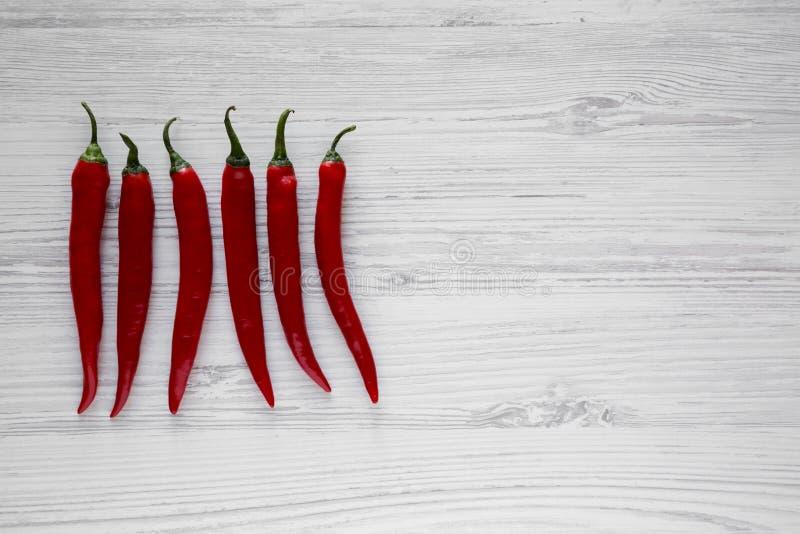 Горячие перцы красного chili на белой деревянной поверхности, взгляде сверху Сверху, надземный скопируйте космос стоковая фотография