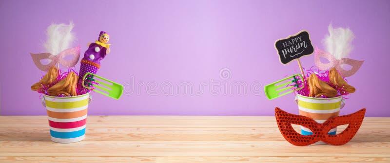 Еврейская предпосылка Purim праздника с ведром, маской масленицы, noisemaker и hamantaschen печенья на деревянном столе стоковое фото