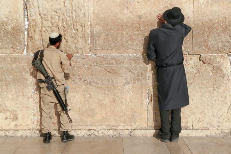 Еврейский солдат и правоверный человек молят на западной стене в городке Иерусалима старом стоковые изображения rf