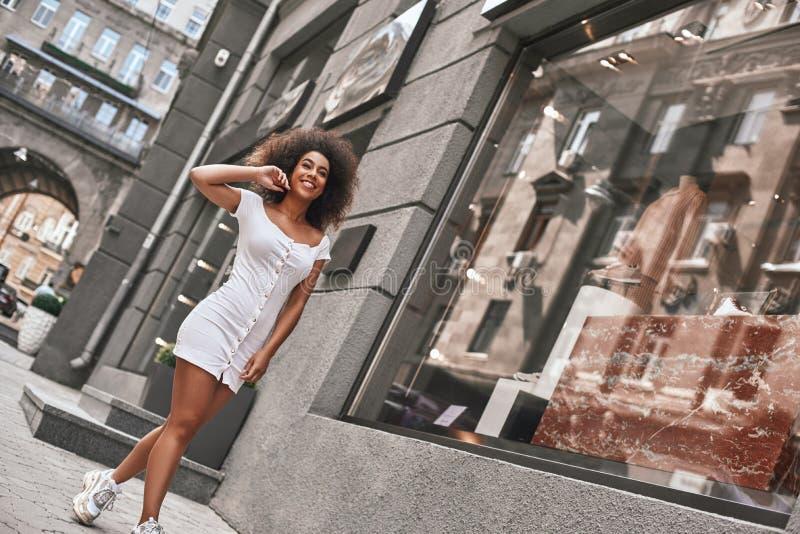 Ежедневный режим Во всю длину красивой афро американской женщины в стильном белом чувстве счастливом и усмехаясь пока идущ стоковые фото