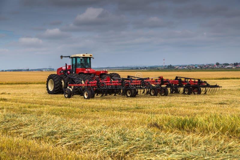 Екатеринбург, РОССИЯ - 23-ье августа 2018: Совместите жатку на работе жать поле пшеницы стоковая фотография