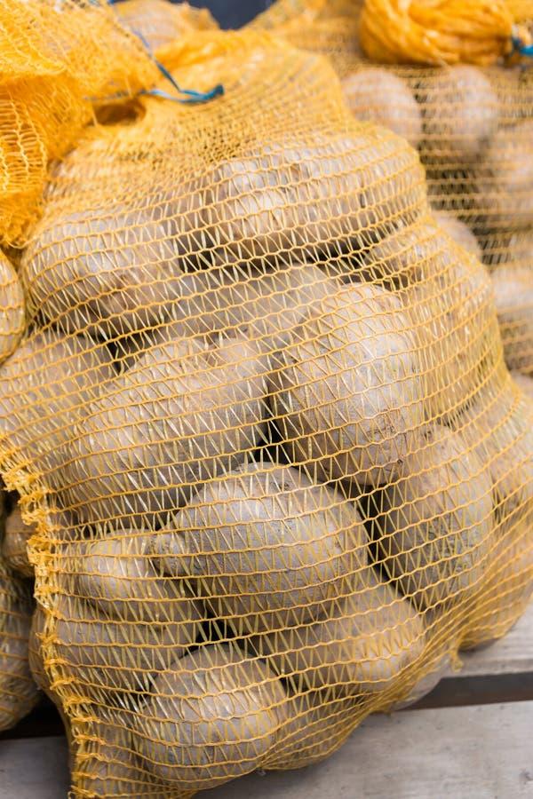 Еда сырцовых картошек в мешках на деревянной предпосылке стоковое фото rf