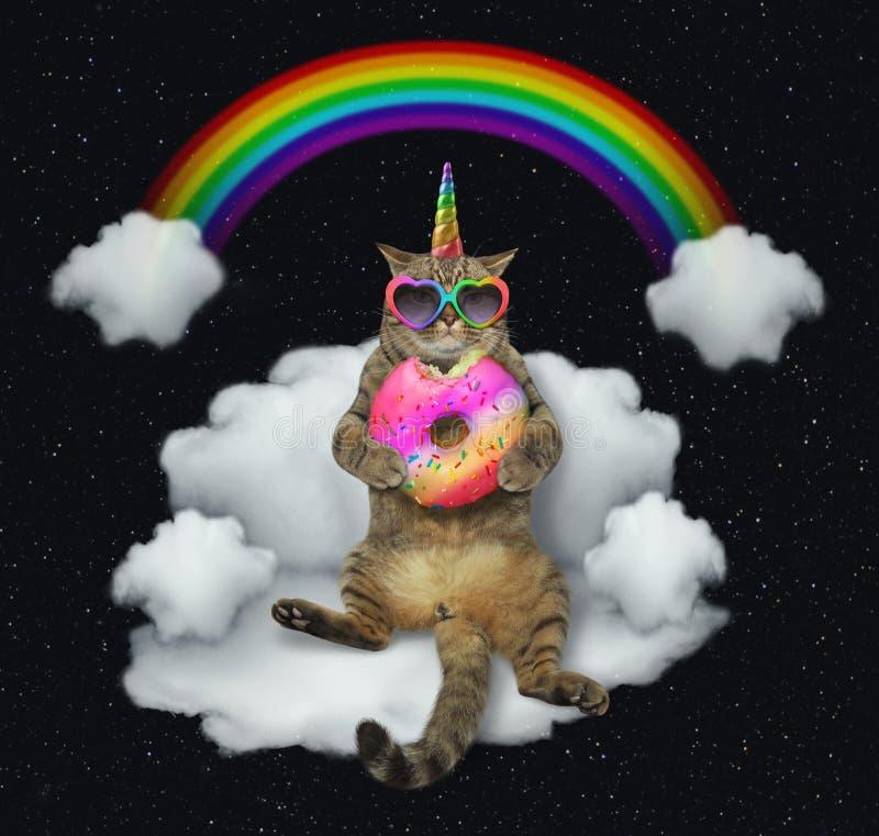 Единорог кота с донутом цвета на облаке стоковые фото