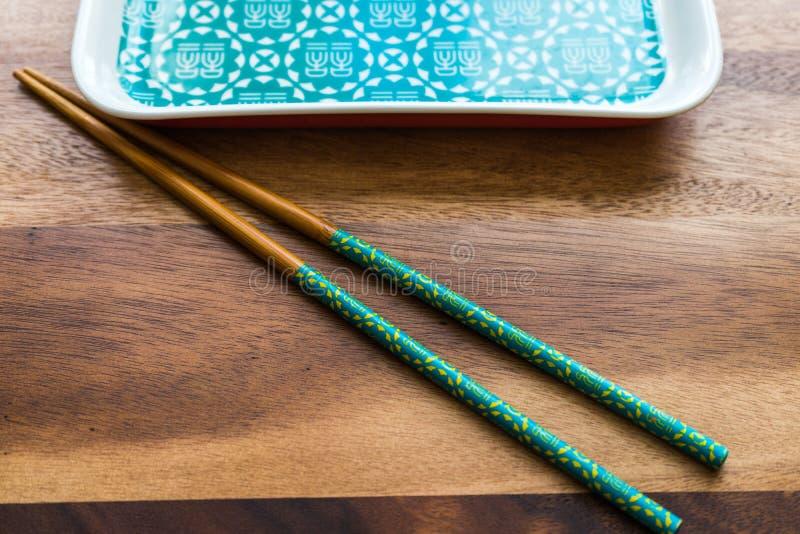 ЕСТЕСТВЕННЫЕ БАМБУКОВЫЕ ПАЛОЧКИ и плита на предпосылке деревянного стола стоковые изображения rf