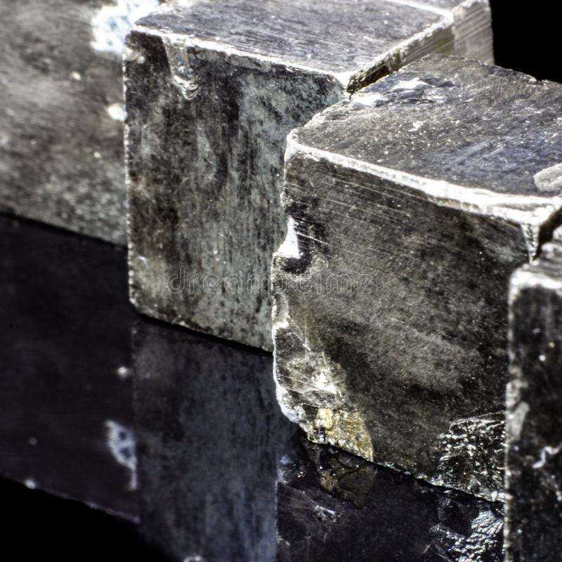 Естественные части кубов пирита на черной предпосылке стоковые фото