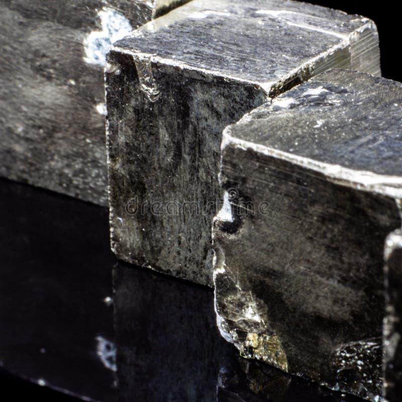 Естественные части кубов пирита на черной предпосылке стоковое изображение
