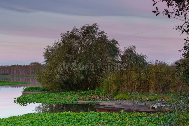 Естественный ландшафт со шлюпками в воде на заходе солнца Изумляя озеро с небольшими artisanal рыбацкими лодками Свет восхода сол стоковое изображение rf